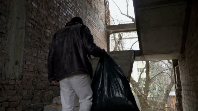 Dirty homeless with garbage bag up stairs in abandoned building video