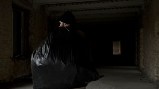 Dirty homeless with garbage bag walks in abandoned building video