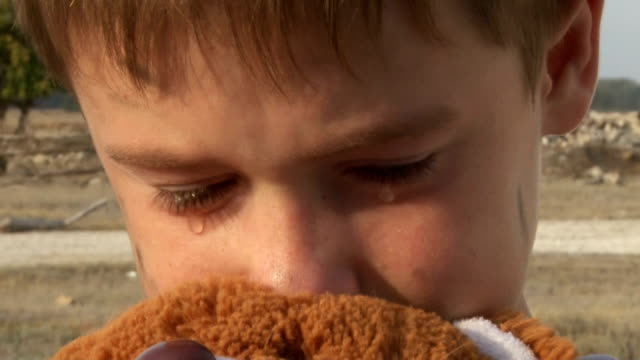 dirty little orphan boy close-up crying and petting a stuffed toy on the background of the ruins of the destroyed houses video