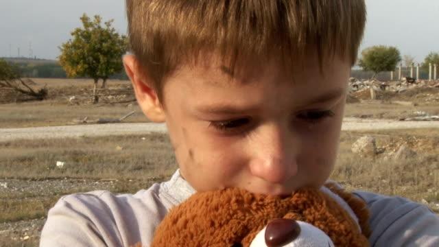 vídeos de stock e filmes b-roll de sujo pouco órfão rapaz close-up chorar e mini de pelúcia brinquedo toalhetes com as lágrimas no fundo das ruínas da floresta casas - teddy bear