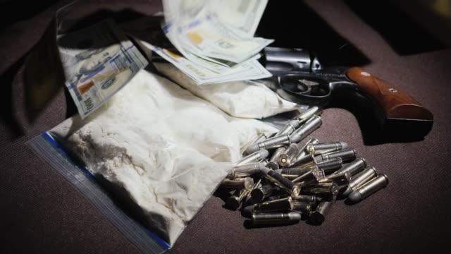 smutsiga pengar koncept. cash us-dollar faller från ovan till en cache av vapen och droger - dirty money bildbanksvideor och videomaterial från bakom kulisserna