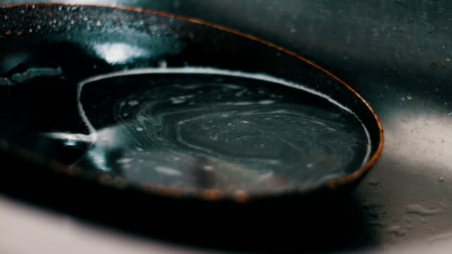 Dirty pan lies in the kitchen sink Dirty pan lies in the kitchen sink with soapy water.Water flows from the top the tap to the pan cooking pan stock videos & royalty-free footage