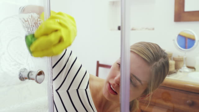 Dirty showers love a little elbow grease 4k footage of an attractive young woman cleaning the shower at home cleaning stock videos & royalty-free footage