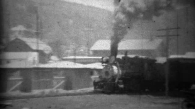 1934: Dirty smoky locomotive train passing small mountain town.