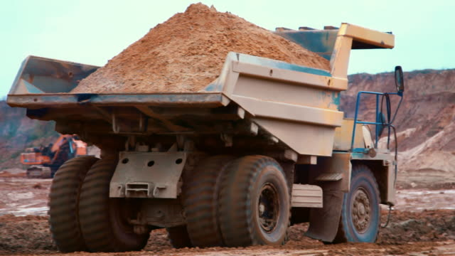 Dirty tipper truck transports sand on road in quarry. Large yellow dumper truck Dirty tipper truck transports sand on road in quarry. Large yellow dumper truck used in modern mine. Heavy machinery in mining industry dump truck stock videos & royalty-free footage