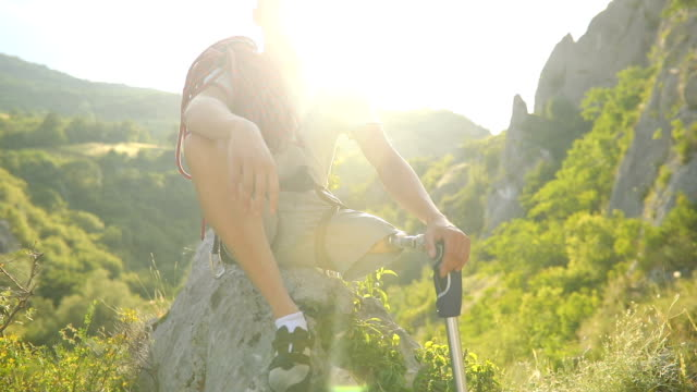 Disability guy climber sitting One man, disability young man hiker with prosthetic leg sitting on a rock in nature. conquering adversity stock videos & royalty-free footage
