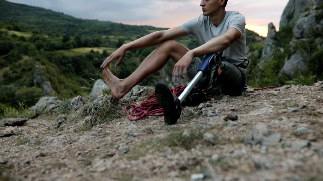 Disability guy resting after climbing One man, disability young man hiker with prosthetic leg, sitting on the floor in nature.. prosthetic equipment stock videos & royalty-free footage