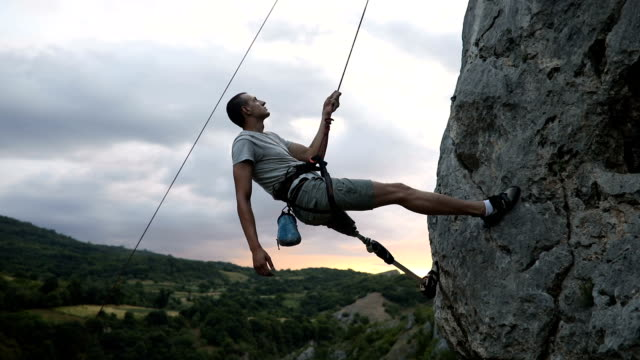 Disability man adrenaline junkie One man, disability young man with prosthetic leg, free climbing on a rock in nature.. conquering adversity stock videos & royalty-free footage