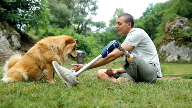 Disability man and best friend One man, disability young man with prosthetic leg with his dog, relaxing together in nature. artificial limb stock videos & royalty-free footage