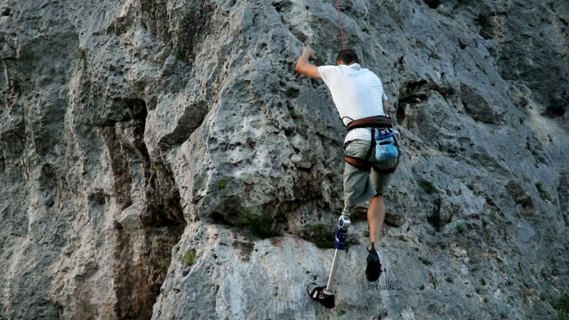 Disability man going climbing One man, disability young man with prosthetic leg, free climbing on a rocky mountain in nature. prosthetic equipment stock videos & royalty-free footage