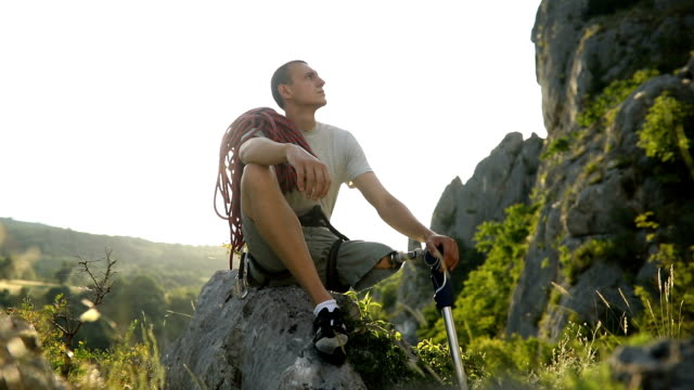 Disability man relaxing on a rock One man, disability young man hiker with prosthetic leg sitting on a rock in nature. amputee stock videos & royalty-free footage