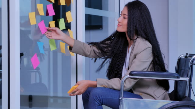 vídeos de stock e filmes b-roll de disabled black women sitting at workplace.creative business women brainstorming ideas working together sharing data in modern glass office.the disability collection 2019 :business & leadership - capacidades diferentes