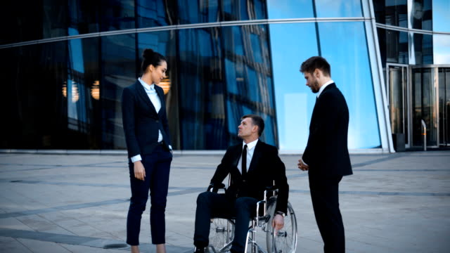 Disabled businessman in wheelchair and two his collegues has positive conversation video