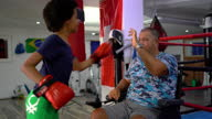 istock Disabled coach is preparing teen girl to kick boxing match 1279385197