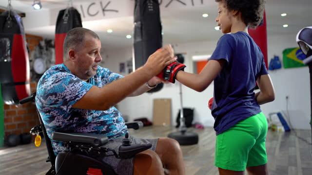 l'allenatore disabile sta preparando la ragazza adolescente per dare il via alla partita di boxe - sparring allenamento video stock e b–roll