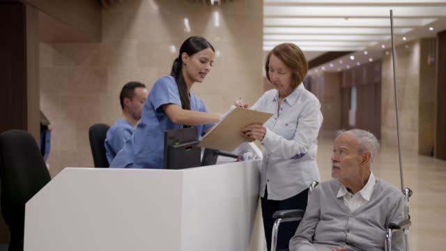 vídeos y material grabado en eventos de stock de anciano discapacitado registrado en el hospital por su compañero en la estación de enfermeras - register