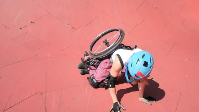 vídeos y material grabado en eventos de stock de mujer discapacitado generación-z en silla de ruedas haciendo acrobacias en el parque de patinaje y cayendo - deportes en silla de ruedas