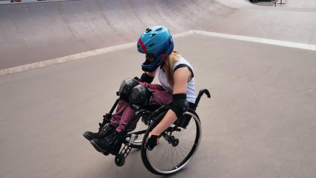vídeos y material grabado en eventos de stock de mujer discapacitado generación-z en silla de ruedas haciendo acrobacias en el parque de patinaje - deportes en silla de ruedas