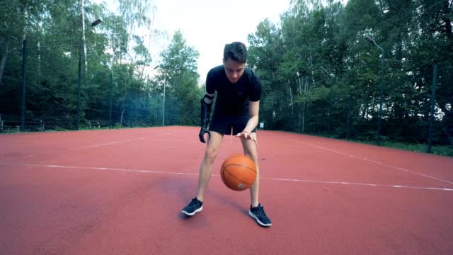 cyborg umano disabile con protesi bionica gioca a basket con il braccio artificiale. 4k. - arto umano video stock e b–roll