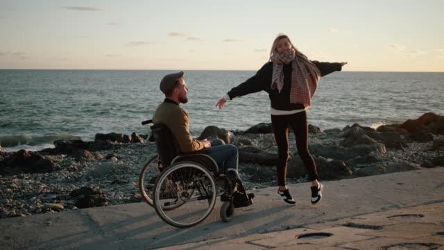 handikappade mannen och hans friska flickvän har kul på havet, dans - fysiskt funktionshinder bildbanksvideor och videomaterial från bakom kulisserna