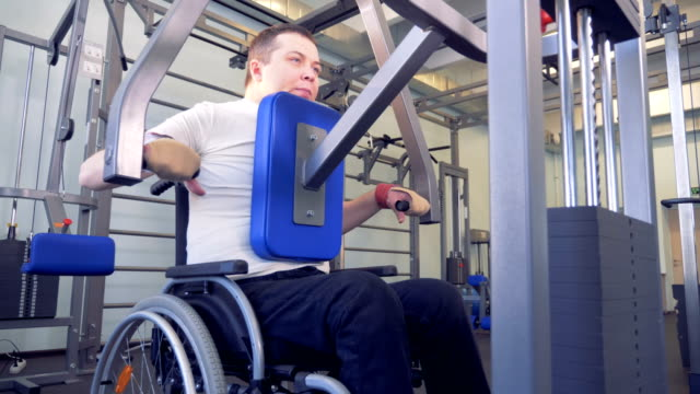 Disabled man does strengths exercises for back on training apparatus. video