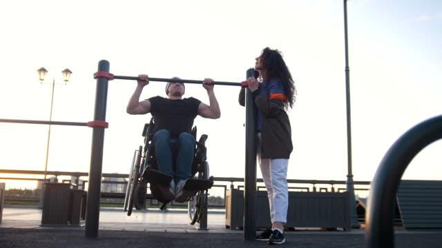 vídeos y material grabado en eventos de stock de hombre discapacitado en silla de ruedas tirado para arriba en la barra junto a la joven al aire libre - deportes en silla de ruedas