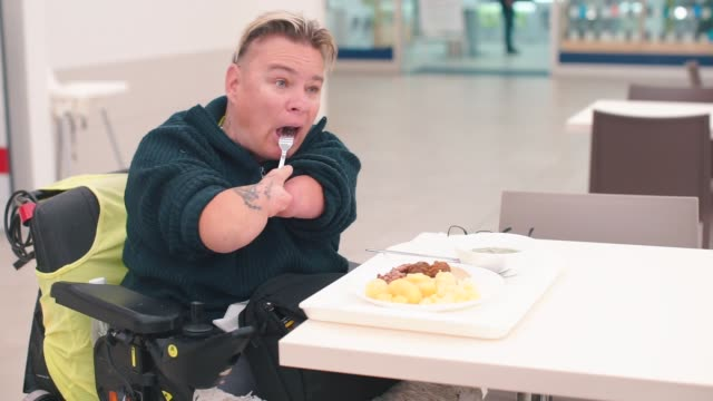 Disabled man, office worker sitting at a table in a restaurant, eating lunch.