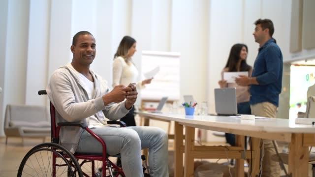 handikappade mannen sitter i en rullstol på arbetsplatsen - fysiskt funktionshinder bildbanksvideor och videomaterial från bakom kulisserna
