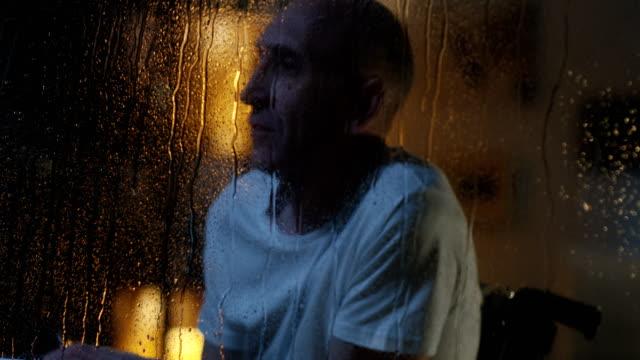vídeos de stock e filmes b-roll de disabled man watching storm - old men window