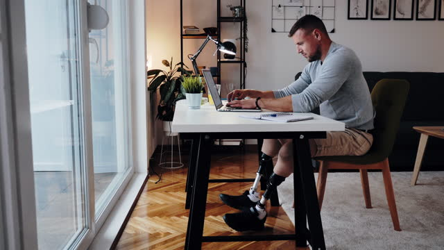 Disabled man with prosthetic legs working from home, panning video left to right Disabled man with prosthetic legs working from home artificial limb stock videos & royalty-free footage