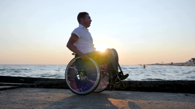 disabled person sitting in wheelchair on embankment, cheerful handicapped man on invalid carriage, crippled male video