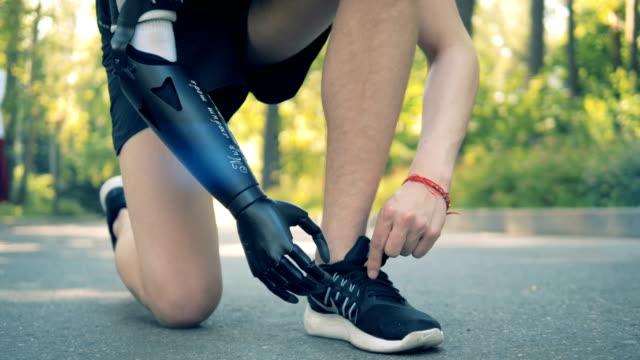 障害者ネクタイスニーカー、クローズアップ。ロボットアームを持つ人間 - 四肢点の映像素材/bロール