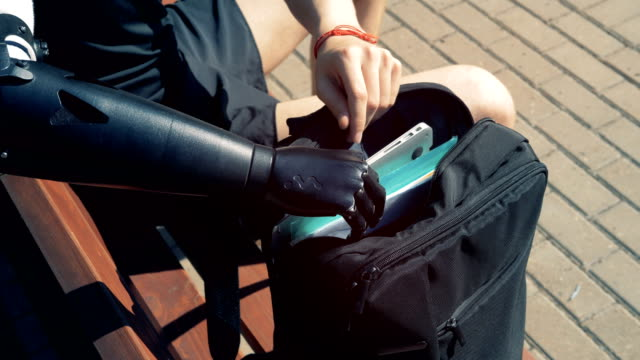 Disabled person with a prosthesis takes his laptop, sitting on a bench. Disabled person with a prosthesis takes his laptop, sitting on a bench. 4K. artificial limb stock videos & royalty-free footage