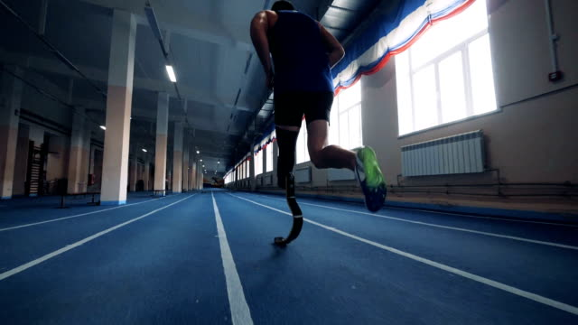 Disabled person with prosthetic leg running, backview. A sportsman with prosthesis running. amputee stock videos & royalty-free footage