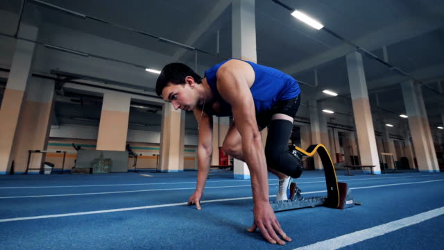 Disabled runner stands in a pose and starts to run, side view. One man running on a track, wearing prosthesis. amputee stock videos & royalty-free footage