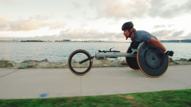 Disabled wheelchair athlete pushing racing chair outside at sunset working out video