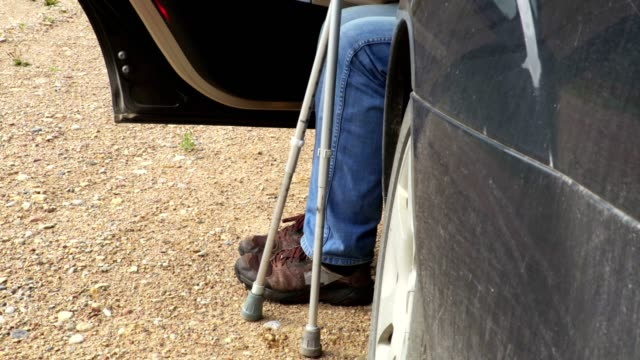 Disabled with crutches get out of car Disabled with crutches get out of car crutch stock videos & royalty-free footage