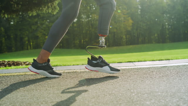 Disabled woman in sports shoes running on road. Girl feet training outdoors Close up disabled woman legs in sports shoes running on road. Girl feet training outdoors in slow motion. Female jogger legs doing cardio workout in park. Runner legs running outside artificial limb stock videos & royalty-free footage