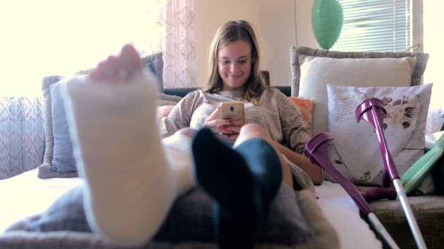 disabled woman with broken leg and plaster foot at home using smart phone - skręcony filmów i materiałów b-roll