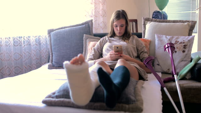 Disabled woman with broken leg and plaster foot at home using smart phone Disabled woman with broken leg and plaster foot at home using smart phone crutch stock videos & royalty-free footage