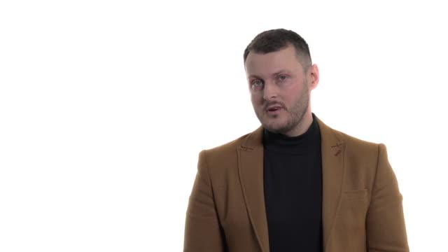 stockvideo's en b-roll-footage met teleurgestelde zakenman die negatieve emoties uitdrukt door wijsvinger aan zijn voorhoofdtempel te plaatsen. lichaamstaal en gebaren concept. portret schot, geïsoleerd, op witte achtergrond - men blazer