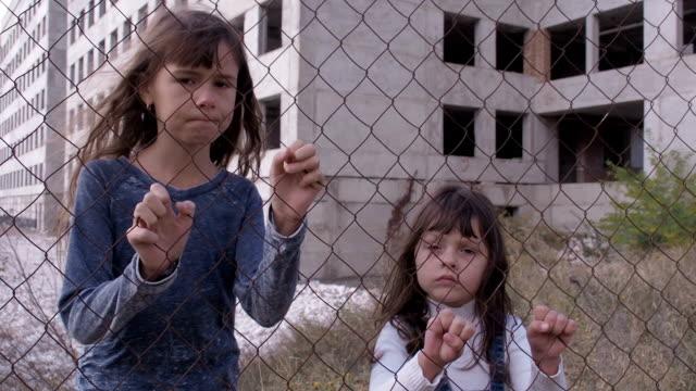 Disappointed children. Disappointed children. Sad little girls behind an iron grid. human trafficking stock videos & royalty-free footage