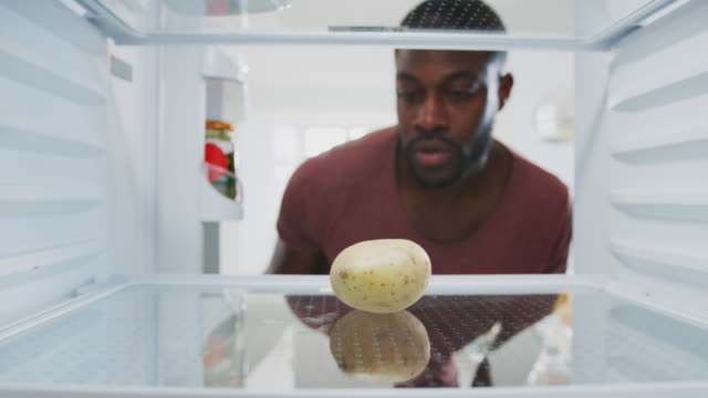 Disappointed Man Looking Inside Refrigerator Empty Except For Potato On Shelf View from inside empty fridge as man opens door and picks up potato before closing door with disappointed expression fridge stock videos & royalty-free footage