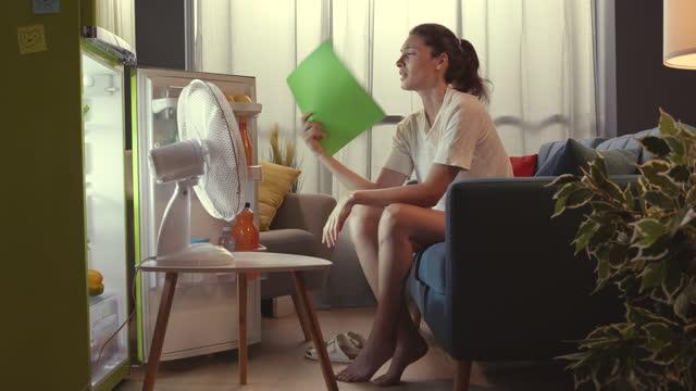 donna delusa sentirsi caldo durante l'estate a casa - ritemprarsi video stock e b–roll