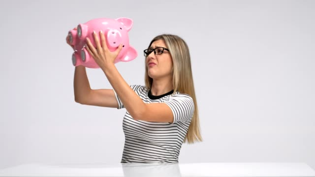 Disappointed woman sitting at a table and shaking a piggybank Disappointed woman sitting at a table and shaking a piggybank against gray background piggy bank stock videos & royalty-free footage