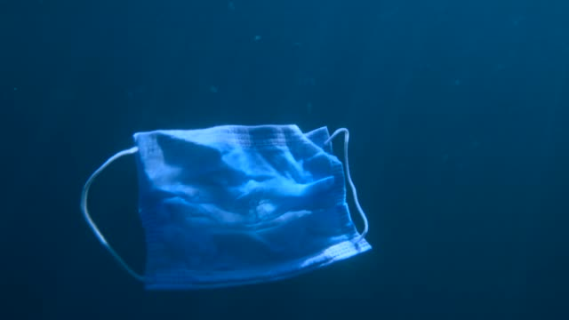 Discarded face mask slowly drifting in blue deep of water column. Coronavirus COVID-19 is contributing to pollution, as discarded used masks clutter polluting seas and ocean along with plastic trash Discarded face mask slowly drifting in blue deep of water column. Coronavirus COVID-19 is contributing to pollution, as discarded used masks clutter polluting seas and ocean along with plastic trash obsolete stock videos & royalty-free footage