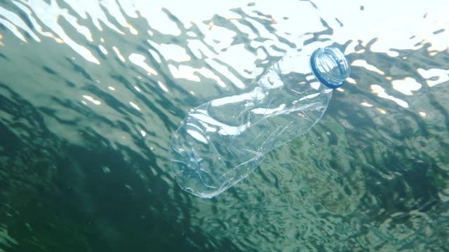 discarded plastic bottle floating in the sea, filmed in 5 X slow-motion. video