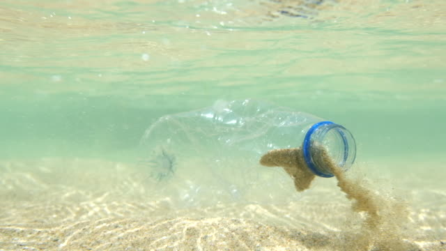discarded used plastic water bottle in the sea, filmed in 5 X slow-motion. video