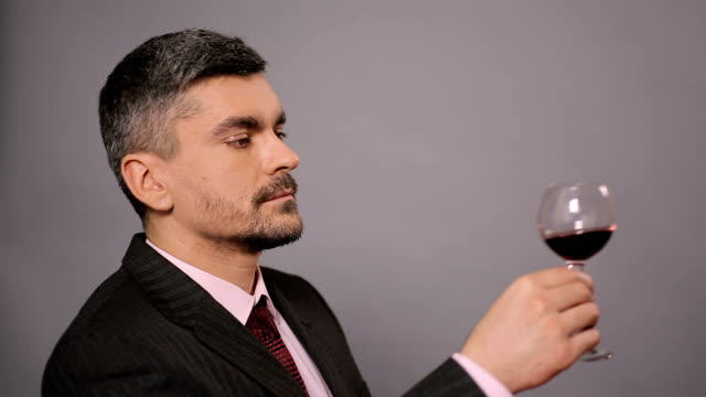 Discontented connoisseur smelling aroma and drinking red wine at restaurant video