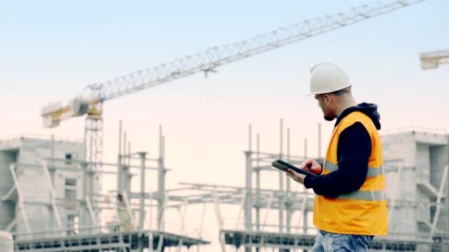 vidéos et rushes de discussion entre un architecte senior et un travailleur sur le chantier - chantier